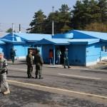 Besucher gehen in die mittlere der drei Barracken